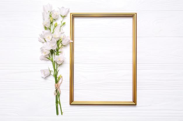 Sinos de flores brancas e uma moldura de ouro sobre fundo branco de madeira.