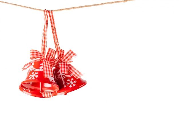 Sinos de natal isolados com fitas de artesanato em uma corda de juta, ano novo