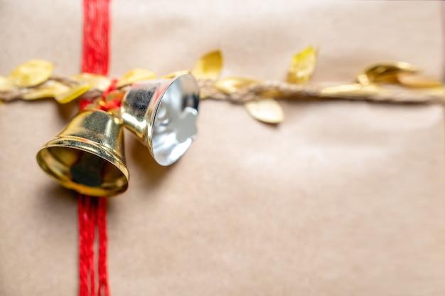Sinos de natal no presente amarrados com corda vermelha e dourada
