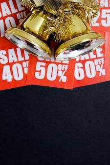 Sinos de ouro em etiquetas de desconto vermelhas