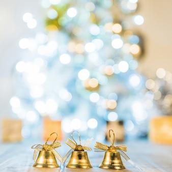 Sinos decorativos perto da árvore de natal