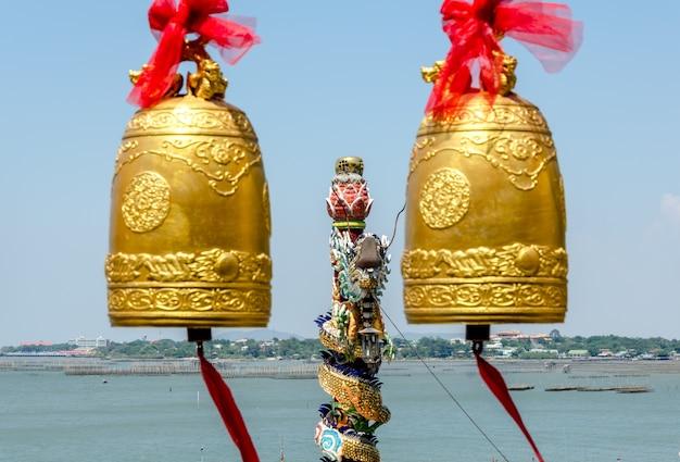 Sinos e estátua de dragão no templo budista da tailândia
