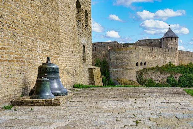 Sinos enormes ao lado da parede do castelo de narva, na estônia.