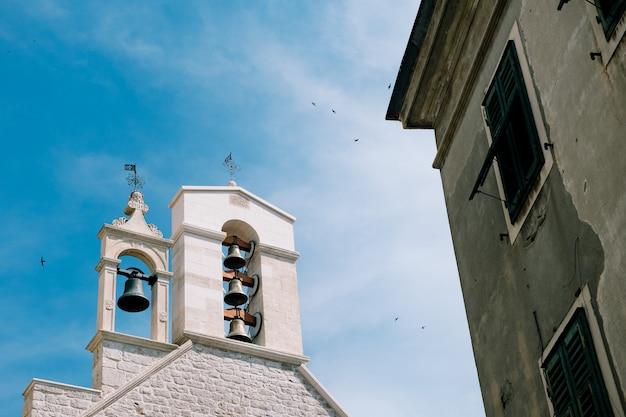 Sinos na torre do sino da catedral em um cenário de céu azul e uma casa vizinha