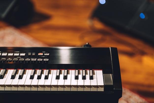 Sintetizador de teclado musical eletrônico com teclas brancas e pretas no estúdio de gravação
