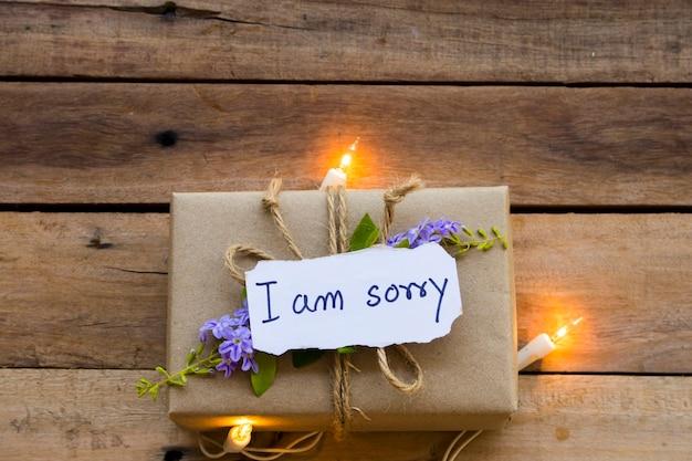 Sinto muito, manuscrito cartão de mensagem com caixa de presente e luz