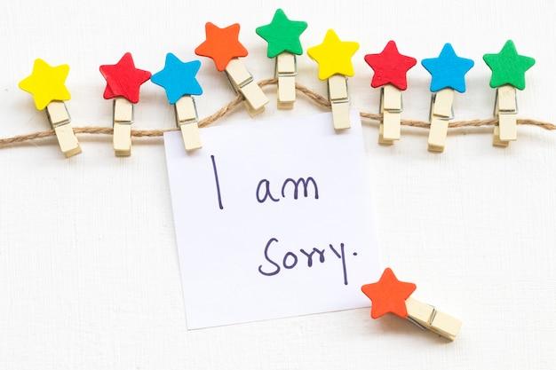 Sinto muito, manuscrito cartão de mensagem com estrela de madeira
