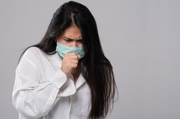 Sintoma de gripe resfriado ou alergia. mulher asiática nova doente que espirra no isolado da máscara no fundo cinzento. cuidados de saúde. foto de estúdio. mulher de negócios usa uma máscara e tosse, livre de espaço de cópia.
