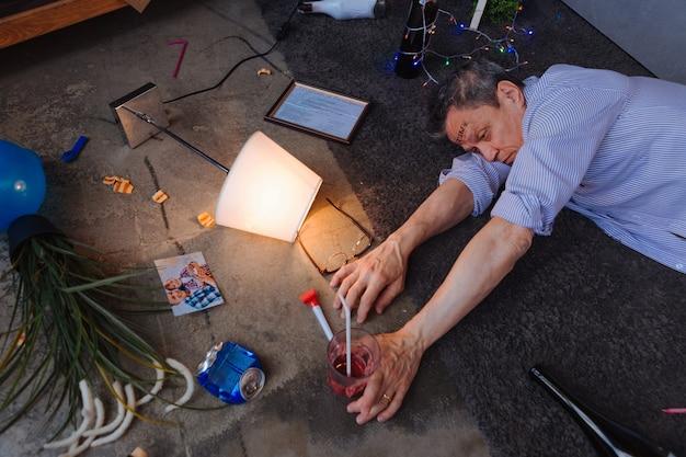 Sintomas de alcoolismo. homem maduro chateado localizando no chão e tomando coquetel