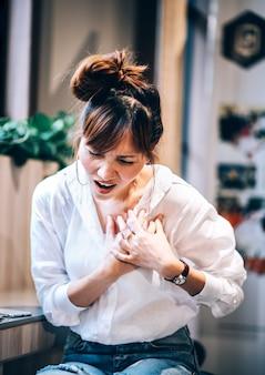 Sintomas de ataque cardíaco a mulher tem dor no peito, precisa de primeiros socorros de emergência, ressuscitação paramédica. conceito de saúde