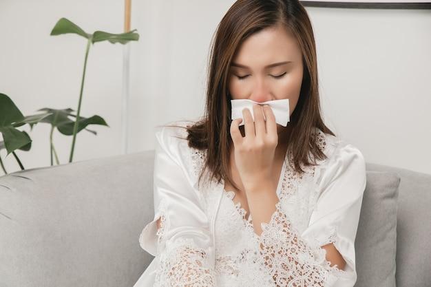 Sintomas de rinite alérgica em mulheres mulher doente em pijamas brancos com resfriado assoando o nariz em um lenço de papel em casa alergias de clima frio