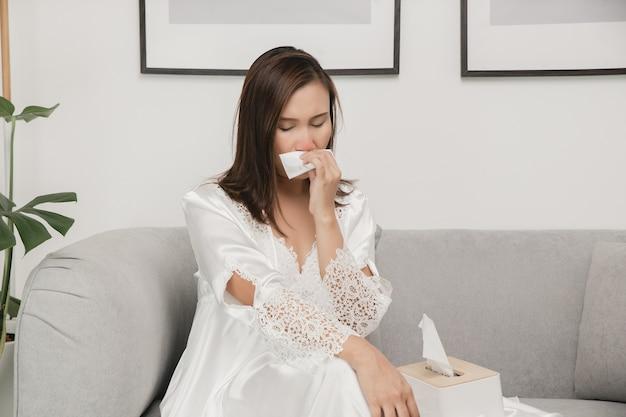 Sintomas de rinite alérgica em mulheres mulher doente, vestindo pijamas brancos, resfriada assoando o nariz em um lenço de papel em casa