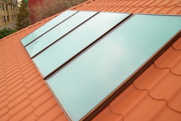 Sistema de aquecimento solar de água (geliosystem) no telhado vermelho da casa.