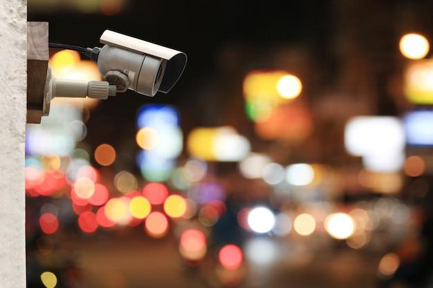 Sistema de câmera cctv no bokeh colorido da estrada à noite, fundo com espaço de cópia.