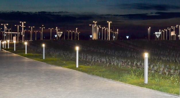 Sistema de iluminação moderno na cidade à noite, lanternas ao longo da estrada.