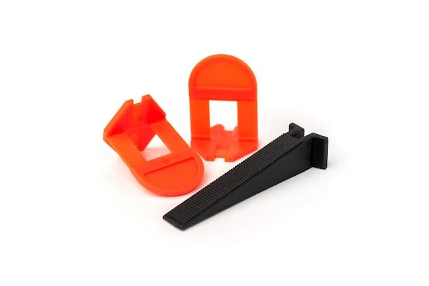 Sistema de nivelamento de azulejos. clipes de plástico e cunhas isoladas no fundo branco.