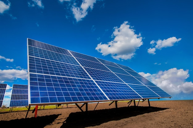 Sistema de painel de estação de energia solar em campo arado e céu com nuvens