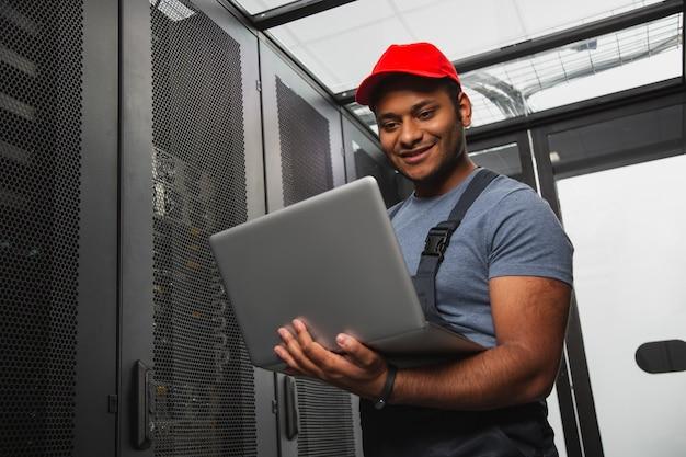 Sistema de ti eficaz. ângulo baixo de um engenheiro de ti alegre, sorrindo e segurando o laptop