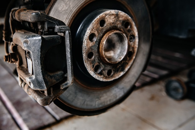 Sistema de travagem da viatura, com travão a disco e pastilha de travão. reparação de suspensão de automóvel na garagem.