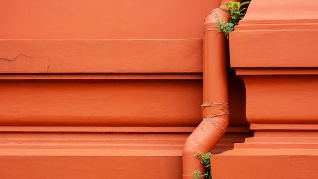 Sistema de tubulação de água plástica instalado no prédio de concreto laranja