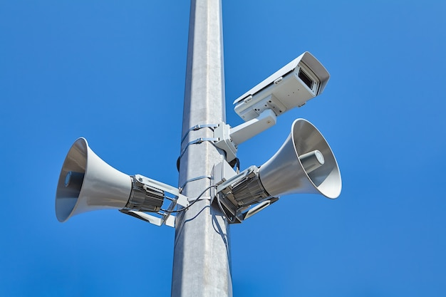 Sistema de videovigilância urbana e rodoviária, bem como alto-falantes públicos montados em poste de aço.