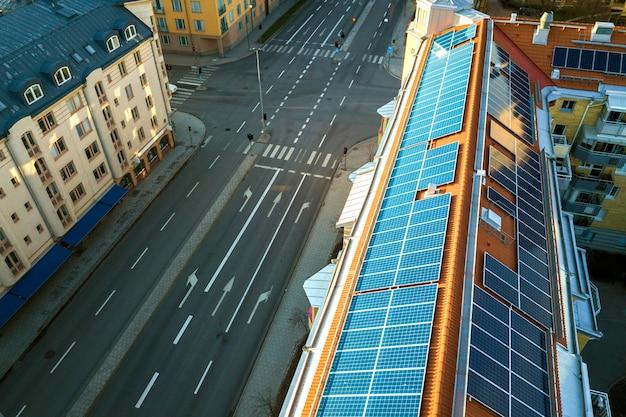 Sistema solar azul dos painéis voltaicos da foto na parte superior superior do telhado do prédio de apartamentos em dia ensolarado
