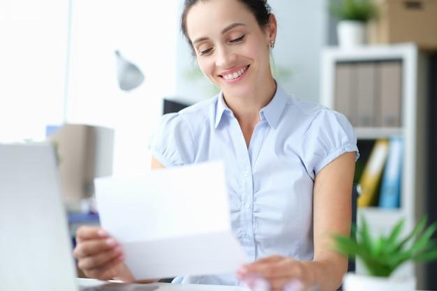 Site de garota feliz do milênio se sente animado lendo boas notícias em uma carta de papelada postal, aproveite Foto Premium