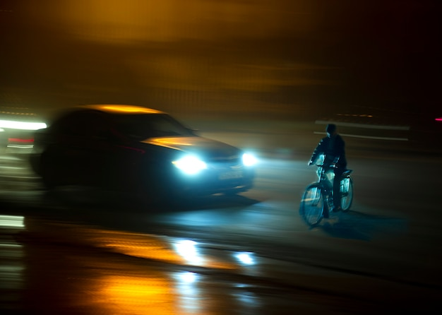 Situação perigosa de tráfego na cidade com ciclista e carro na cidade à noite em um desfoque de movimento