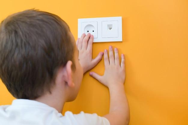 Situação perigosa em casa. criança brincando com uma tomada elétrica. mãos alcançam a tomada elétrica