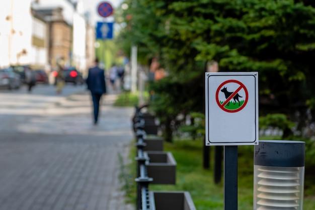 Situado ao lado da rua, há um sinal que proíbe cães de passear pela área verde