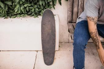 Skate de madeira perto do menino sentado no banco