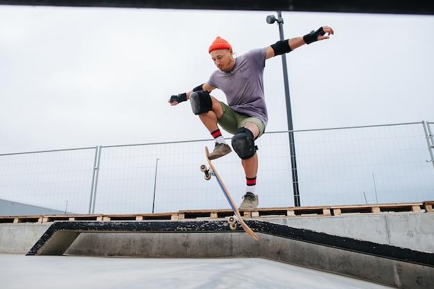 Skatista ágil e maduro com um boné de relógio fazendo manobras com um skate em uma rampa de uma pista de skate. ângulo para cima, pairando no ar com a placa inclinada.