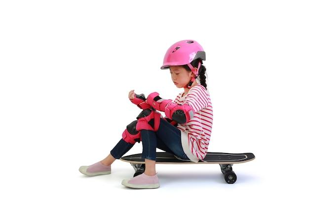 Skatista de criança menina asiática sentado no skate com segurança e equipamento de proteção isolado no fundo branco. imagem com caminho de recorte
