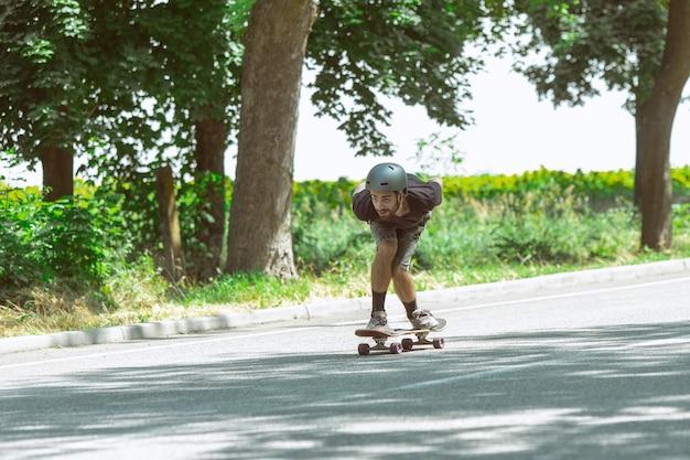 Skatista fazendo um truque perto de prado em dia ensolarado. jovem em equipamento de equitação e longboard no asfalto em ação. conceito de atividade de lazer, esporte, radical, hobby e movimento.
