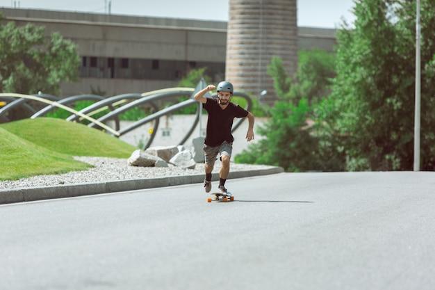 Skatista fazendo uma manobra na rua da cidade em dia ensolarado. jovem em equipamento de equitação e longboard no asfalto em ação. conceito de atividade de lazer, esporte, radical, hobby e movimento.