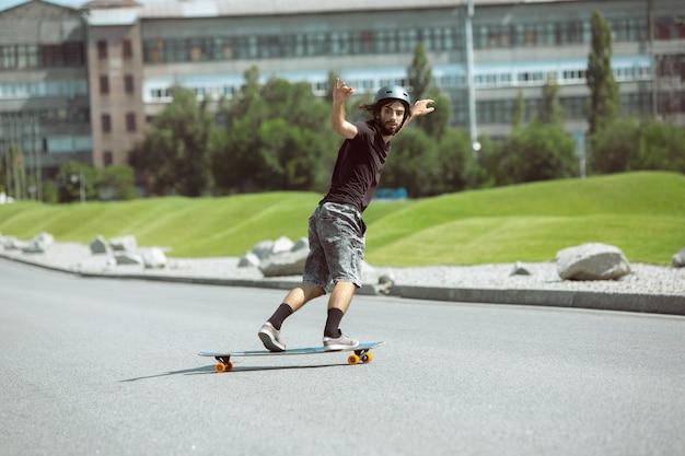 Skatista fazendo uma manobra na rua da cidade em dia ensolarado.