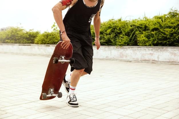 Skatista fazendo uma manobra na rua da cidade em dia nublado. jovem de tênis e boné e longboard no asfalto. conceito de atividade de lazer, esporte, radical, hobby e movimento.