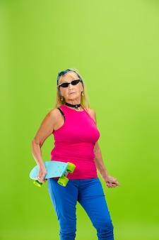 Skatista. mulher sênior em traje ultra moderno, isolado em fundo verde brilhante. parece elegante e moderno, para sempre jovem. mulher madura caucasiana em óculos de sol, roupas brilhantes e tênis.