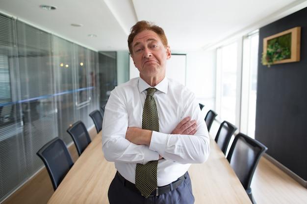 Skeptical, sênior, homem negócios, ficar, sala ...