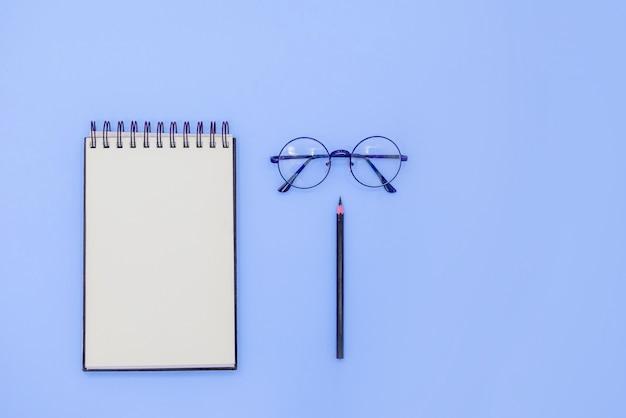 Sketchbook espiral simulado até óculos e lápis preto.