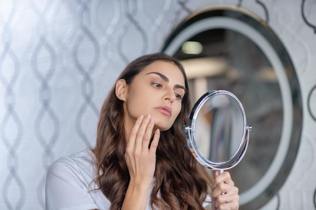 Skicare. uma mulher verificando a saúde de sua pele enquanto se olha no espelho