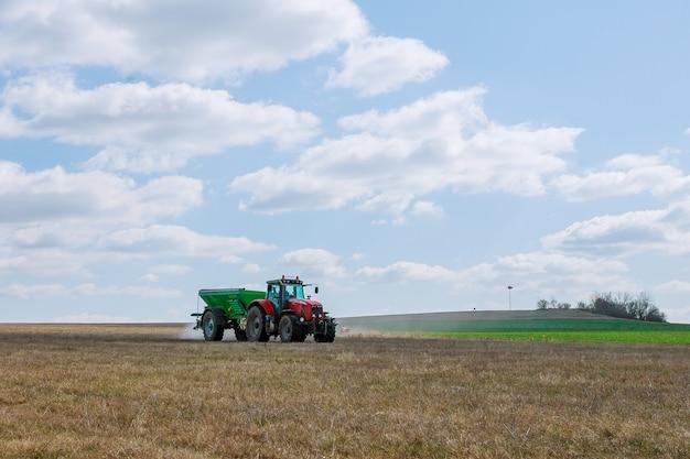 Skutc, república tcheca - 23 de março de 2020: trator espalhando fertilizante no campo de grama. trabalho agrícola.