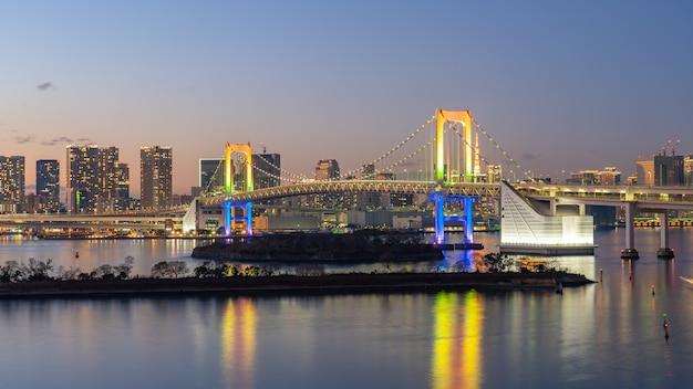 Skyline da cidade de tóquio à noite com vista da ponte do arco-íris