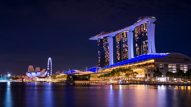 Skyline do edifício do negócio de singapura no alvorecer com reflexão no waterbay no tempo crepuscular. marina iluminada areia da baía à noite