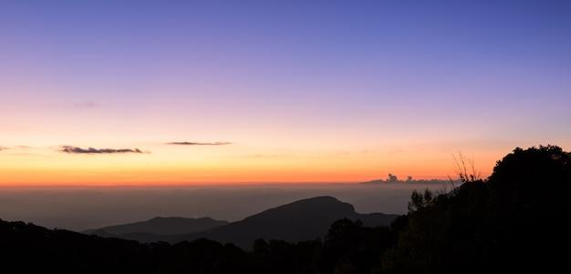 Skyline do nascer do sol dramático sobre montanhas