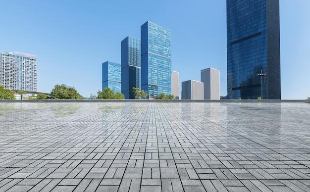 Skyline panorâmica e edifícios com piso quadrado de concreto vazio
