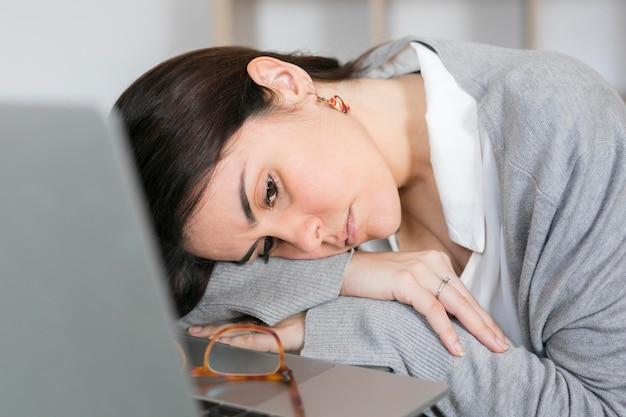 Sleepig mulher de close-up na mesa de vidro perto de laptop