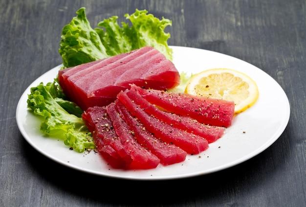 Slicesfield com sashimi de atum rabilho cru no prato branco em madeira est