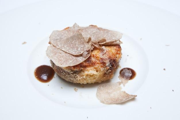 Slide de cogumelo de trufa branca na comida na chapa branca. o cogumelo de trufa branca é a rainha do cogumelo.