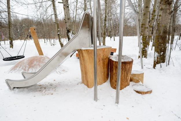 Slide infantil com tocos em vez de escada. cidade de madeira. paisagem de inverno. ideia criativa.